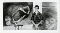 Student posing with paintings