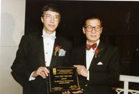 Two men pose with a 10th Anniversary Award of Merit from the Education Foundation