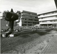 Students sitting on lawn in front of Administration wing and science wing