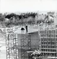 Construction of original Andrews building, view of two workers on scaffold