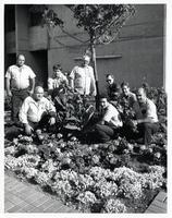 Grounds crew posing amongst the plants behind the Humanities Wing