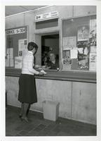 Photograph of woman mailing a package at Canada Post kiosk