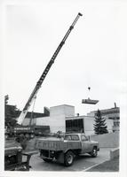 Construction of original Andrews Building showing crane and trucks