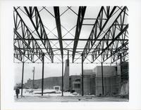 Construction of original Andrews building, view of smoke stacks, steel scaffolding, and construction workers
