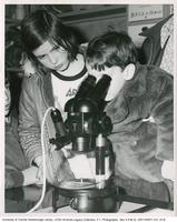 Young Visitor Looking Through Microscope